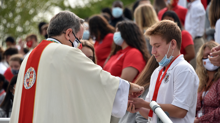 Bishop McClory distributes the Eucharist at an all-school Mass at Andrean Sept. 14, 2020